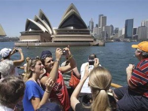 Travelers take in the view and snap photos as they pass by the Sydney Opera House while riding on a harbor ferry in Sydney, Tuesday, Jan. 6, 2009. Though a charter cruise can cost thousands, instead, why not take one of the ferries that shuffle workers to and from downtown each day? (AP Photo/Rick Rycroft)